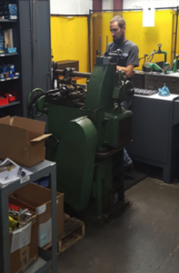 Machine shop worker at gear hobs machine
